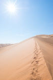 Cenic ridges of sand dunes with footprints in Sossusvlei, Namib Naukluft National Park, best tourist and travel attraction in Nami. Bia. Adventure and Stock Photo