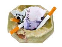 Cenicero con el dinero y los cigarrillos Imagen de archivo libre de regalías