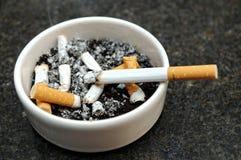 Cenicero con topes y el cigarrillo ardiente Fotos de archivo