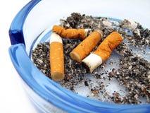 Cenicero de cristal azul con el cigarrillo Foto de archivo libre de regalías