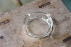 Cenicero de cristal vacío en la tabla de madera Fotografía de archivo