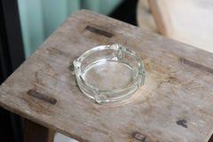 Cenicero de cristal vacío en la tabla de madera Fotos de archivo