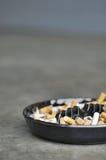 Cenicero lleno de cigarrillos en la tabla, primer Fotografía de archivo libre de regalías