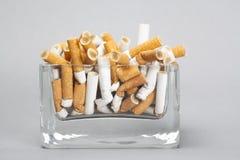 Cenicero por completo de cigarrillos en fondo gris Imagen de archivo