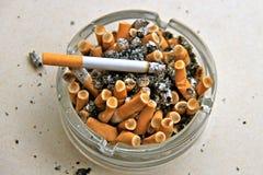 Cenicero por completo de los cigarrillos Fotografía de archivo