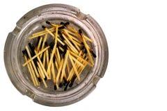 Cenicero sucio viejo con los partidos quemados, aislados en el backgrou blanco Foto de archivo libre de regalías