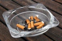 Cenicero y cigarrillos en fondo de madera Imagenes de archivo