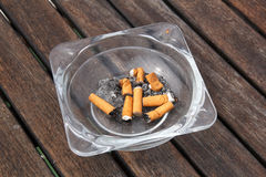 Cenicero y cigarrillos en fondo de madera Imágenes de archivo libres de regalías