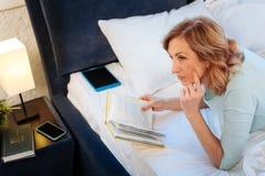 Cenna z włosami kobieta odpoczywa w niedokończonym łóżku z hardcover książką obraz royalty free