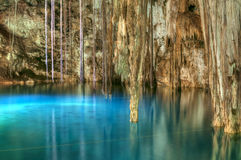 Cenote Xkenken. Beautiful clear blue water of Xkenken cenote in Dzitnup, Mexico illuminated from above with tree roots and stalactites hanging from ceiling of stock photos
