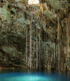 Cenote Xkenken. Beautiful natural pool of Cenote Xkenken in underground cavern with crystal clear blue water and vines and stalactites hanging from ceiling in stock photo