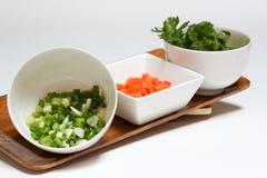 A cenoura cortou o vegetal no copo branco no fundo branco imagem de stock