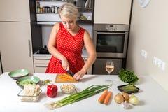 Cenoura do corte da jovem mulher e preparação para o frigideira chinesa vegetal Imagem de Stock