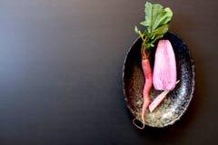 Cenoura vermelha crua e rabanete cor-de-rosa partido ao meio, vista direita, superior, no prato traseiro oval foto de stock