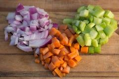 Cenouras, cebola, e aipo cortados em uma placa de corte de madeira Imagens de Stock