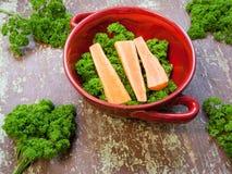 Cenouras com folhas verdes em um fundo de madeira Imagens de Stock