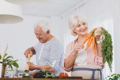 Cenouras de sorriso da posse da mulher mais idosa imagem de stock
