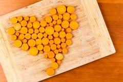 Cenouras desbastadas arranjadas na forma do coração imagens de stock