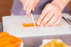 Cenouras do corte do cozinheiro com uma faca cerâmica Imagem de Stock Royalty Free