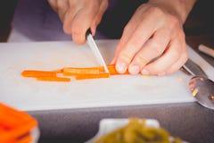Cenouras do corte do cozinheiro com uma faca cerâmica Foto de Stock