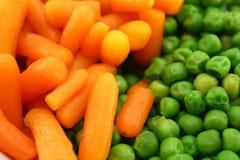 Cenouras e ervilhas verdes Fotos de Stock Royalty Free