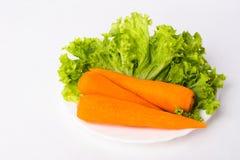 3 cenouras e folhas da alface em uma placa branca imagem de stock