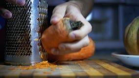 Cenouras em um ralador friccionado na cozinha home Movimento lento video estoque