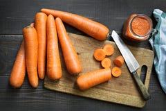 Cenouras frescas com suco de cenouras com placa e faca de corte no fundo de madeira Foto de Stock