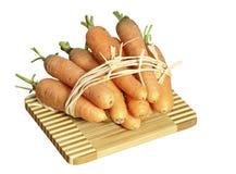 Cenouras frescas em uma placa em um fundo branco Fotos de Stock Royalty Free