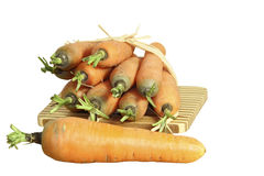 Cenouras frescas em uma placa em um fundo branco Imagem de Stock Royalty Free