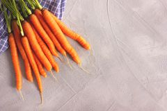 Cenouras frescas inteiras cruas no fundo cinzento imagem de stock