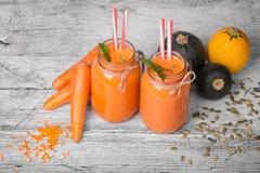 Cenouras, sementes de abóbora e abobrinhas em um fundo de madeira Sucos naturais das cenouras e das laranjas com hortelã aromátic fotografia de stock royalty free