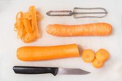 Cenouras, uma faca e um descascador vegetal em uma placa de desbastamento branca fotos de stock