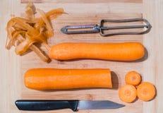 Cenouras, uma faca e um descascador vegetal em uma placa de desbastamento de madeira fotos de stock royalty free