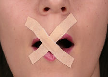 Censored. A young woman is censored with tape over her mouth Stock Photos