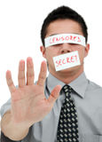 Censored secret. Young businessman with band on his eyes and mouth showing his hand to us Royalty Free Stock Images