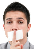 Censored speech. A handsome young man with his finger over his mouth, which is sticked down with a white tape Royalty Free Stock Images