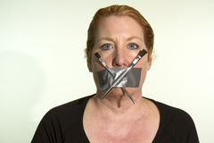 Censoring the Arts. Censorship of the arts or artists expressed by a woman with duct tape and paint brushes over her mouth royalty free stock image