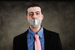 Censorship. Portrait of a businessman having the mouth closed with tape Stock Photography