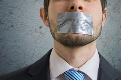 Censorship concept. Man is silenced with adhesive tape on his mouth.  royalty free stock photos