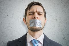 Censorship concept. Young man is silenced with duct tape over his mouth.  Royalty Free Stock Photos