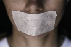 Censorship in the Modern World. A man`s mouth sealed with an adhesive tape, close-up stock photography