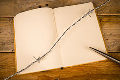 Censorship. Notebook and pen with barbed wire, a press censorship concept royalty free stock photography