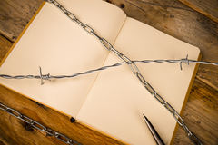 Censorship. Notebook and pen with barbed wire, a press censorship concept stock photography