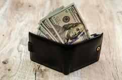 Cent billets d'un dollar dans un portefeuille noir photos libres de droits