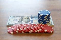 Cent billets d'un dollar et jetons de poker sur la table en bois Images stock