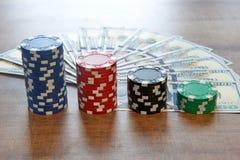 Cent billets d'un dollar et jetons de poker sur la table en bois Image stock