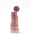1 cent coin falling from stack of euro coins Stock Photos