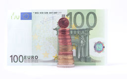 1 cent coin standing on top of stack of euro coins near 100 euro bank note. Stock Photography