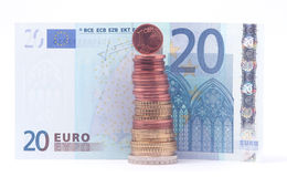 1 cent coin standing on top of stack of euro coins near 20 euro bank note Stock Image